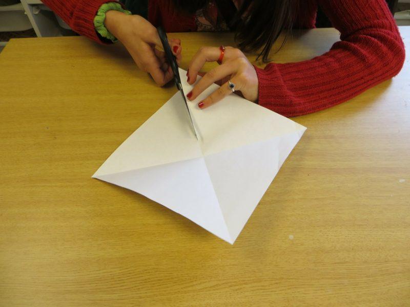 ハサミで紙を切る女性
