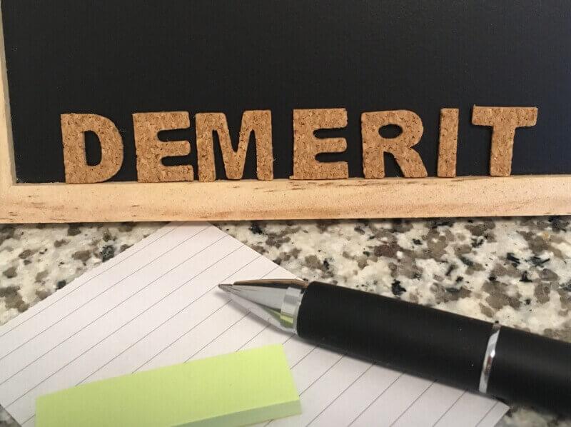 DEMERITという文字とボールペンと付箋