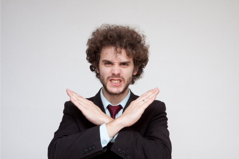 手で×マークを作る険しい表情の男性