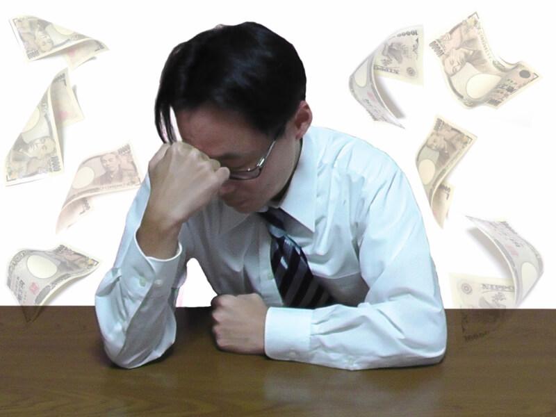 お金の事で悩み頭を抱える男性