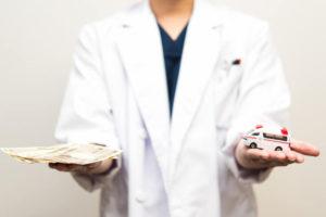 お金と救急車のミニチュアを手のひらに乗せている医師